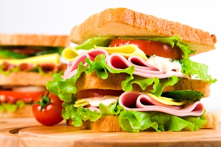 bologna baloney: big sandwich with fresh vegetables on wooden board on white background Stock Photo
