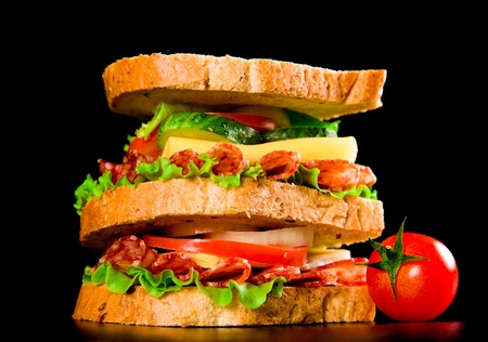 big sandwich with fresh vegetables on black background photo