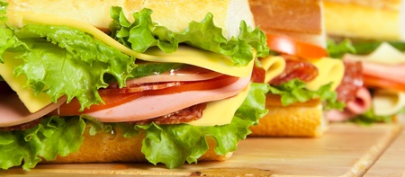 big sandwich with fresh vegetables on wooden board photo