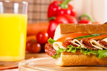 big sandwich with fresh vegetables and juice on wooden board photo