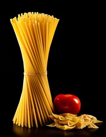 spaghetti: spaghetti en tomaat geïsoleerd op zwarte achtergrond Stockfoto