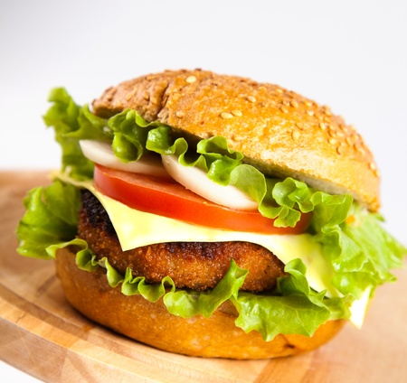 cutlet: hamburger with fish cutlet and vegetables on wooden board Stock Photo