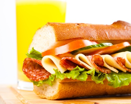 big sandwich with fresh juice on wooden board photo