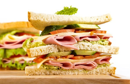 big sandwich with fresh vegetables on wooden board on white background Stock Photo - 12185454