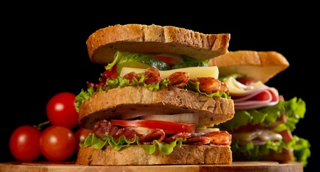 big sandwich with fresh vegetables on wooden board on black background photo