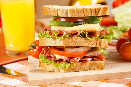 big sandwich with fresh vegetables on wooden board on table photo
