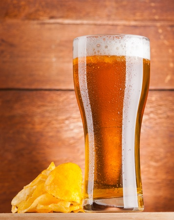 glass of fresh golden beer with potato chips photo