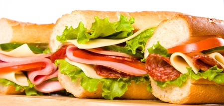 bologna baloney: big sandwich with fresh vegetables on wooden board