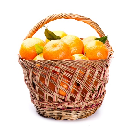 tangerines with leaves in basket isolated on white photo