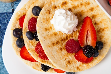 pancakes with fresh ripe berries and whipped cream photo