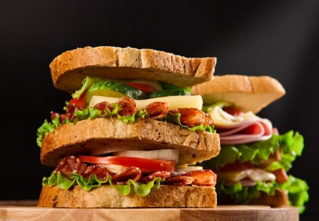 big sandwich with fresh vegetables on wooden board black background photo