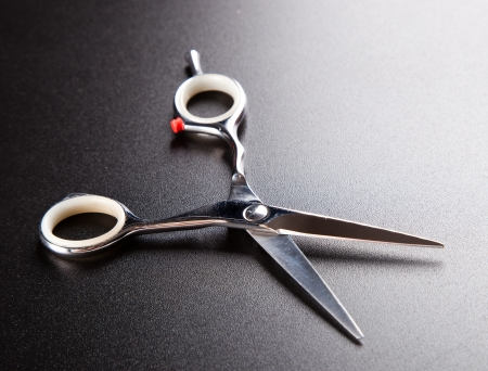 professional hairdresser scissors on  dark background photo