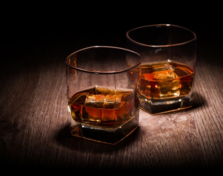 whiskey in glasses on wooden table Archivio Fotografico