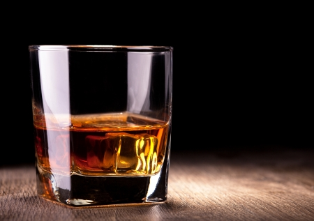glass with whiskey on wooden table Stockfoto