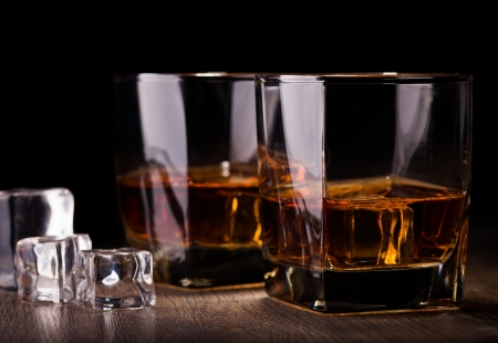 glass with whiskey on wooden table Standard-Bild