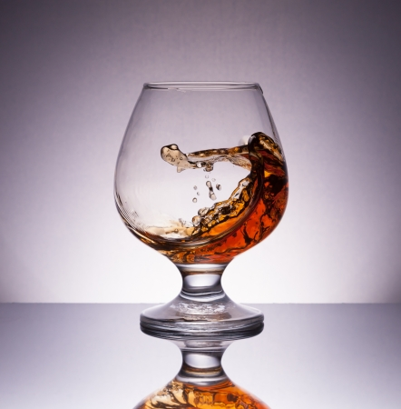 splashing cognac in glass with reflection