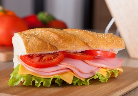 big sandwich on wooden cutting board photo