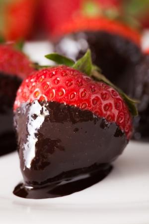 chocolate covered strawberries: macro fresas cubiertas de chocolate en una fila, profundidad de campo
