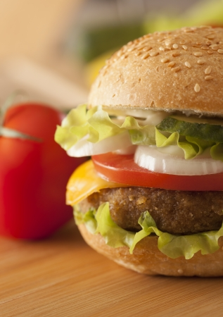 juicy hamburger with vegetables on table photo
