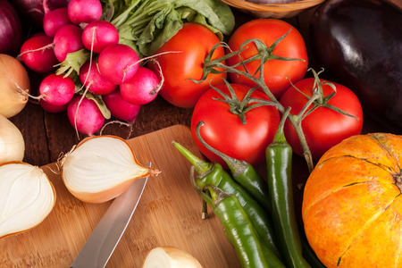 colorful vegetables and cutting board on wooden table photo