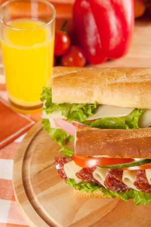 salame: big sandwich with fresh vegetables and juice on wooden board Stock Photo