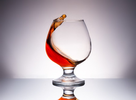 splashing cognac in glass with reflection photo