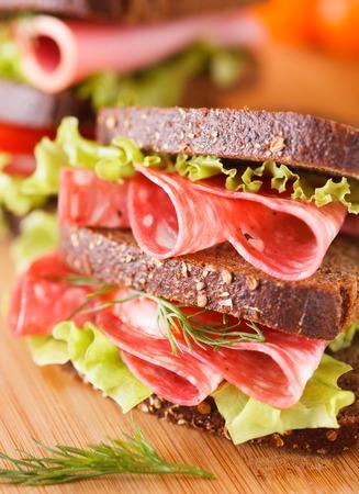 big sandwich on wooden cutting board photo