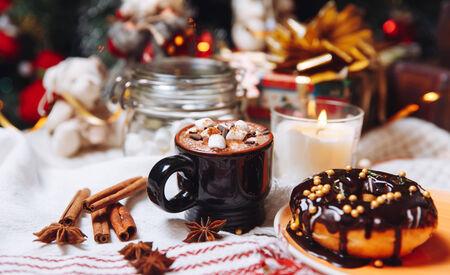 velas de navidad: dulces navideños de colores y bebidas calientes en la tabla de vacaciones cerca del árbol de Navidad Foto de archivo