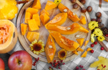pumpkin pieces on a wooden cutting board surrounded flower arrangements photo