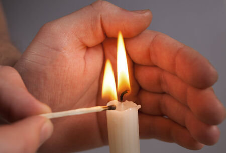 kindle: Hands Kindle candle Stock Photo