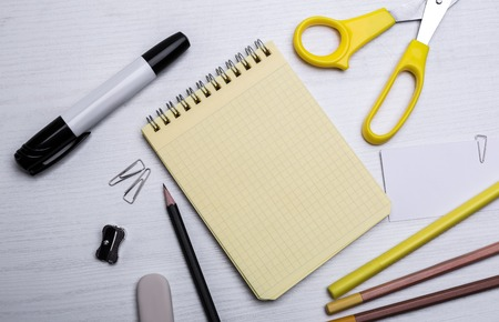 writing materials: yellow notebook in a cage and scissors and markers others writing materials on the white wooden table
