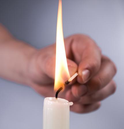kindle: kindle candle match hand closeup on white background