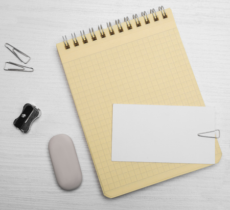 writing materials: yellow notebook in a cage and others writing materials on the white wooden table Stock Photo
