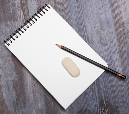 diagonal diary education: pencil and eraser on the edge of white notebook on a wooden table