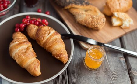 orenge: croissant with the red currant berries and the orange jam in the little jar Stock Photo