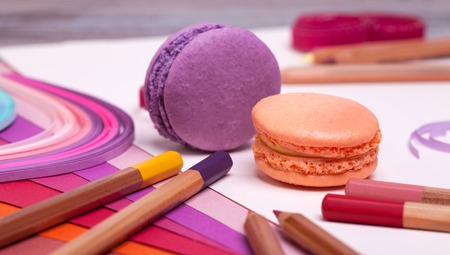 paper sheets: pencils and paper sheets and macaroons on a wooden table