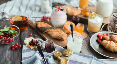 orenge: many cream mousses and jams on a wooden table near buns and hot tea for breakfast