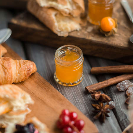 orenge: little jar of orange jam on the wooden table near spices and croissants for breakfast