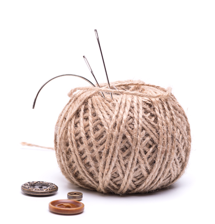 skein: a needle stuck into the skein of  brown thread and a few buttons on a white background