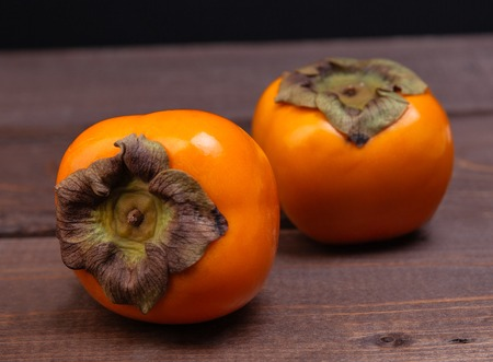 persimmons: two persimmons on a wooden table