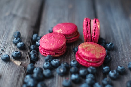 sweet table: fresh macaroons and ripe blackberry on a wooden background Stock Photo