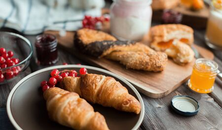 orenge: croissants with the red currant on the brown plate Stock Photo
