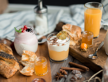 orenge: cream mousse with a physalis and cream mousse with a mint and red currant and buns and jams for breakfast on a wooden table Stock Photo