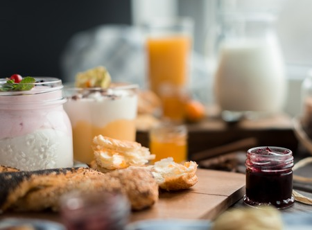 orenge: different cream mousses with berry and buns for breakfast on a wooden table Stock Photo