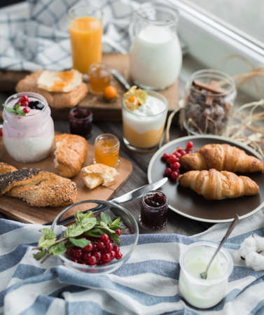 orenge: fresh red currant and mint and glass bowl and berry jam and croissants for breakfast with flowera of cotton on a wooden table Stock Photo