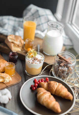 orenge: two croissants on brown plate and cream mousse in the little glass and spices in jar on the wooden table
