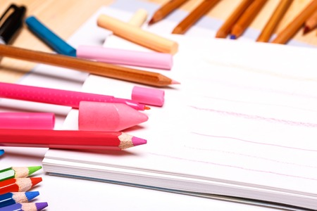 pink stripes: various drawing tools around white notebook and painted pink stripes lying on a wooden table