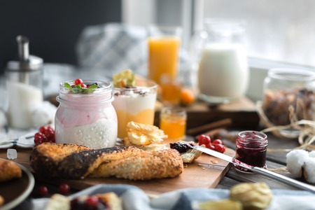 orenge: different cream mousses with berry and sweet jams, and buns for breakfast and tea on a wooden table Stock Photo