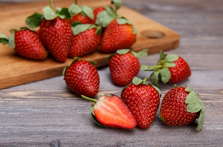 red color: ripe strawberries on a wooden cutting board and on wooden background