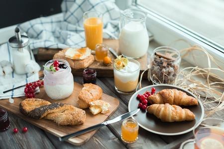 desayuno: bollos con semillas de amapola y crema de la crema batida con grosella y menta fresca sobre una mesa de madera